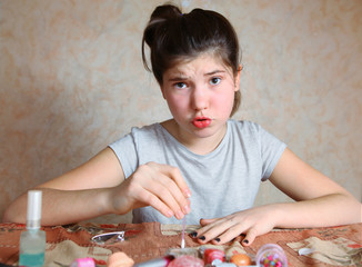 beautiful angry preteen girl make manicure with black nail ename