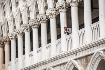 photographer between the arcs in Venice in Italy