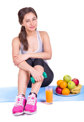 girl on the carpet with dumbbell and fruit