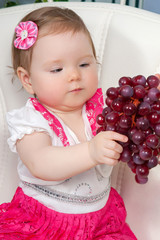 Little baby girl with grapes