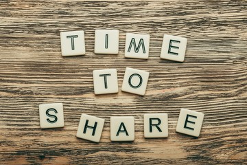 Share. Time to Share text on a wooden background