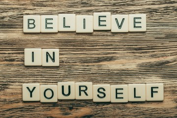 Self. Phrase always believe in yourself, over wooden background
