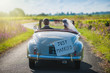 canvas print picture - A newlywed couple is driving a retro car, rear view