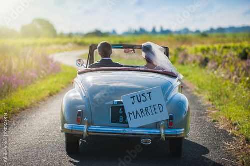 canvas print picture A newlywed couple is driving a retro car, rear view