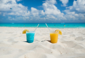 Colorful drinks on sandy beach