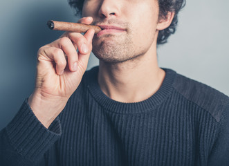Young man smoking a cigar