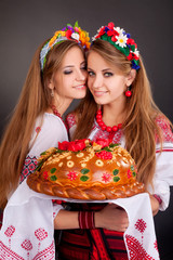 Young women in ukrainian clothes, with garland and round loaf