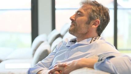 Mature man relaxing at home in sofa