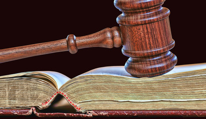 Legal decisions - wooden gavel atop old book