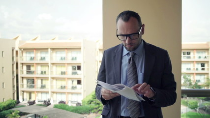 Handsome businessman working with documents standing on terrace