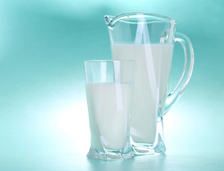 Pitcher and glass of milk on blue background