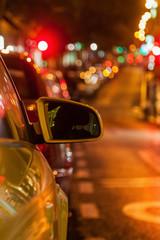 nächtliche Straße mit engem Fokus auf einen Rückspiegel