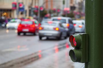 Fußgängerampel mit unscharfer Verkehrsszene im Hintergrund