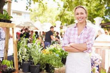Woman Selling Herbs And Plants At Farmers Food Market