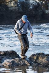 Active senior man at the ocean balancing on boulders