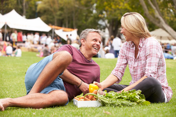 Couple With Fresh Produce Bought At Outdoor Farmers Market