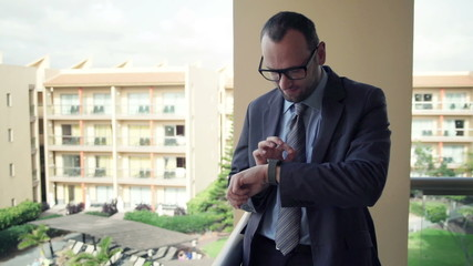 Young businessman with smartwatch while standing on terrace