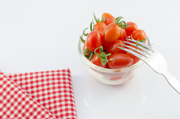 Red Cherry Tomatoes in bowl with fork and red kitchen napkin