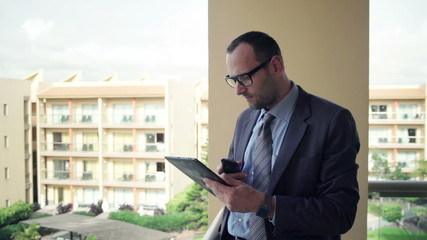 Businessman comparing data on tablet computer and smartphone on