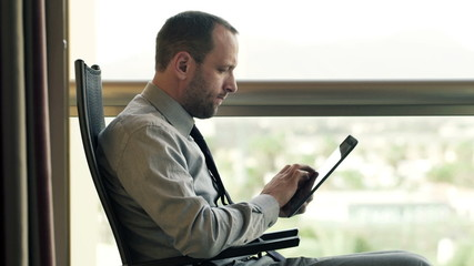 Young businessman working on tablet computer sitting on terrace