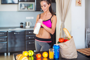 active sportive woman standing in kitchen and healthy food fresh