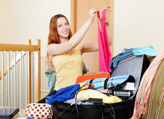 european woman choosing clothes for vacation