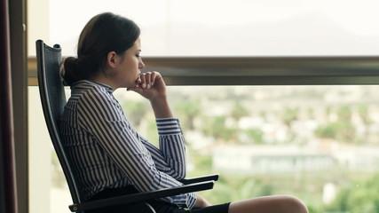 Pensive, sad businesswoman sitting on terrace