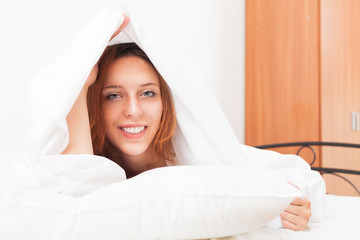 Smiling red-haired woman under the white sheets in bad
