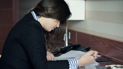 Young businesswoman signing documents sitting by desk at home