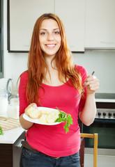 positive girl eating boiled potatoes