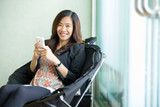 young asian woman sit and use her smart phone poster