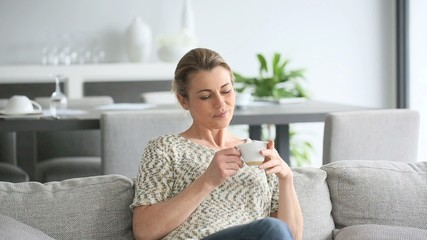 Woman relaxing in sofa, husband and son coming to her