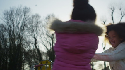 Two young girls playing in a park in slow motion