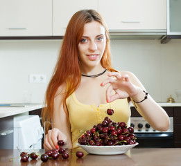 woman with cherry in domestic kitchen
