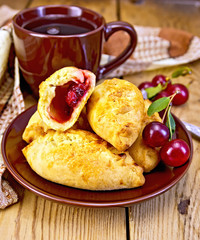 Pies with cherry and mug on board