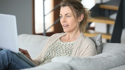 Woman sitting in sofa websurfing on internet with laptop
