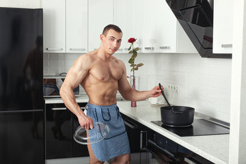 Bodybuilder in the kitchen near stove.
