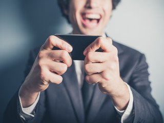 Happy businessman laughing at his smartphone