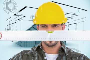 Composite image of handyman looking at spirit level
