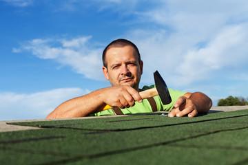 Man finishing installing the bitumen roof shingles