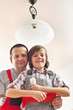 Son helping father changing a lightbulb
