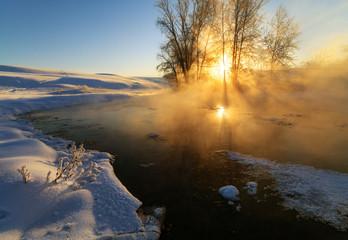 the sun illuminates the beautiful fog on the river in winter