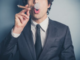 Young businessman blowing smoke rings
