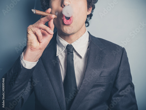 Young businessman blowing smoke rings - 80895466
