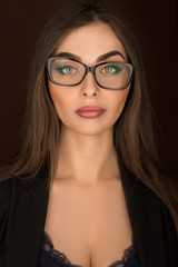 portrait of a business woman with glasses and a black suit