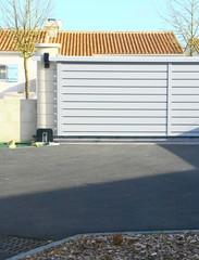 portail alu gris sur cour de maison
