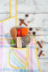 Set of kitchen utensils in pocket of apron on wooden background