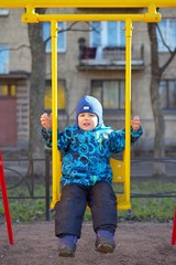 The little boy at a playground shakes on a swing