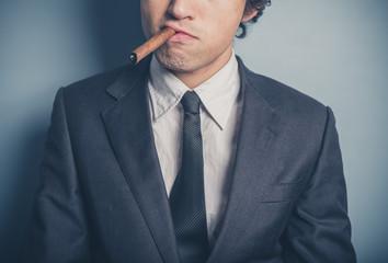 Young businessman smoking a cigar