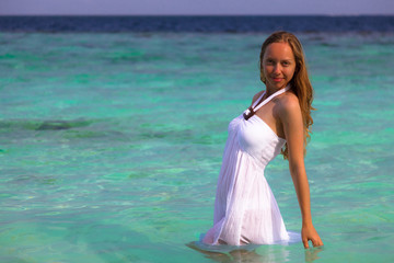 Beautiful girl in white dress standing in water at Maldives